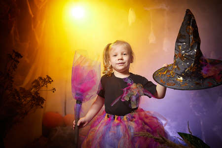 Little cute blonde girl looking as witch in special dress and hat in room decorated for Halloween. Witchcraft and wizardry in carnival. Halloween style photo shoot. Stockfoto