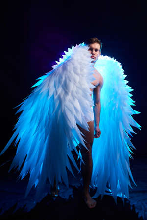 Handsome young athletic man with a bare torso who looks like an angel with white wings. Model dancer posing in a dark studio on black background