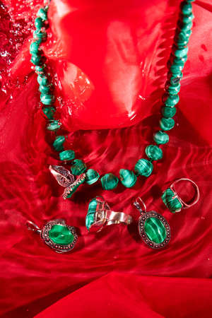 Jewelry from green malachite. Malachite beads in studio on red surface with water