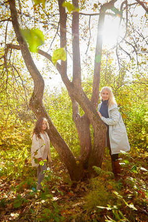 Mother and young little girl with blonde hair in an autumn park on a yellow and orange leaf background. Family walking in forest