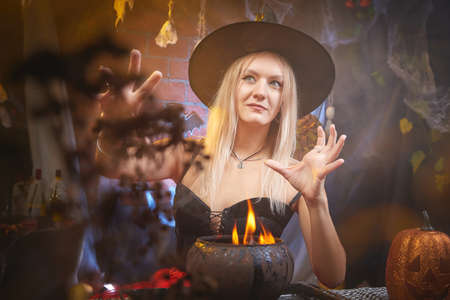 Young woman looking like witch having fun on Halloween in a dark room with yellow light and smoke. Carnival concept and Halloween party