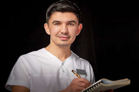 A young man who is a medical doctor in a white uniform poses against a black background in the studio with a notepad in hand