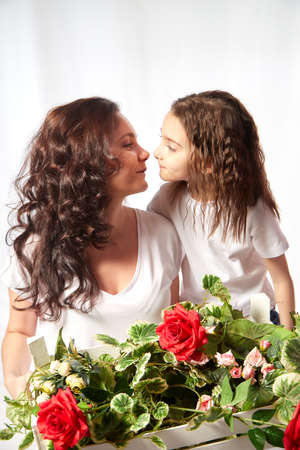 Daughter and mother with flowers in the studio on a white background. Teenager girl and woman posing indoors. Family during photo shoot in summer or spring time