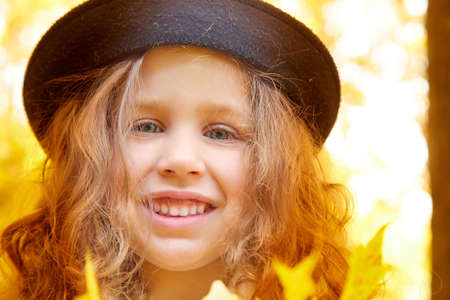Portrait of young funny girl with blonde curly hair and in black hat in an autumn park on a yellow and orange leaf background