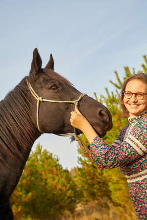 Rural girl with long curly hair and big brown horse in autumn day