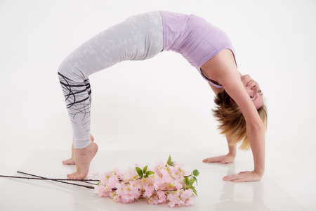Girl doing yoga with beautiful flowers in a studio with a white background