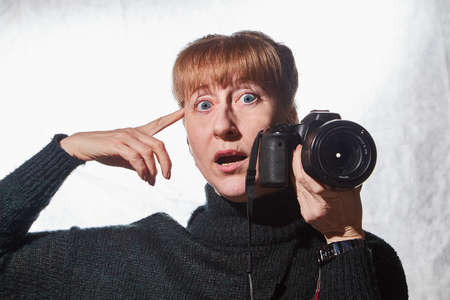 Female photographer in a studio in black dress with camera on white background. Woman posing indoors with cam