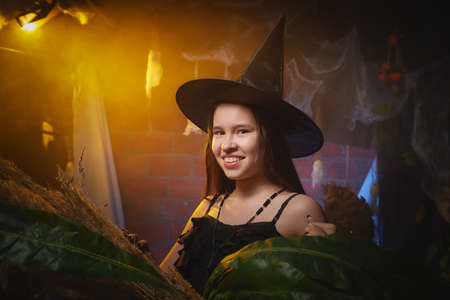 Young girl looking like witch having fun on Halloween in a dark room with yellow light and smoke. Teenager in Carnival and Halloween party