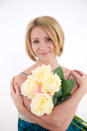 Pretty skinny girl with beautiful flowers on a white background in photo studio