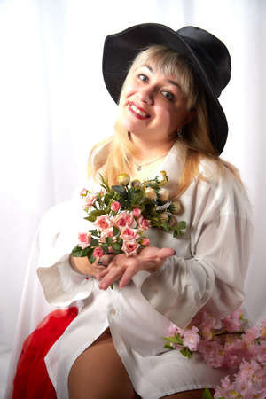 Happy beautiful woman with long blond hair and in black hat posing with flowers in studio on white background Stockfoto