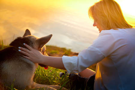 Portrait of middle-aged woman near lake or river and her dog german shepherd during beautiful yellow sunset with sun above the horizon and reflection in the water