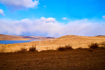 Nature landscape with golden field, wather, hills and blue sky with white clouds in a day or evening