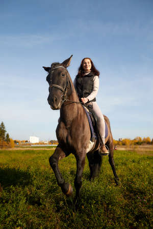 Woman riding a horse in filed in autumn day and blue sky background