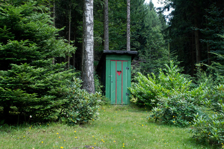 Rural old outhouse in summer photo