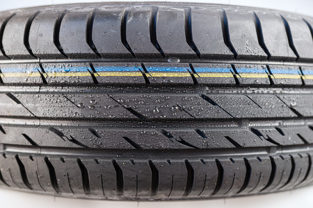 tread: Close-up shot of classical tire tread in wet weather condition Stock Photo