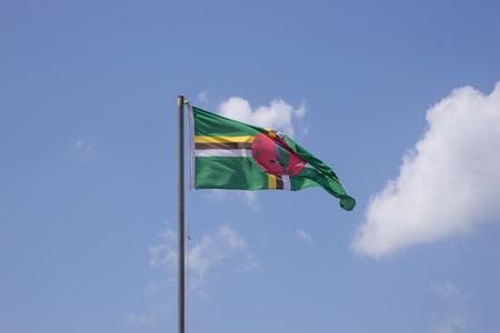 dominica: Flag of Dominica on flagpole over blue sky