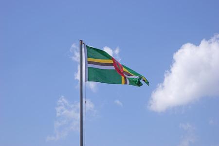 flyaway: Flag of Dominica on flagpole over blue sky