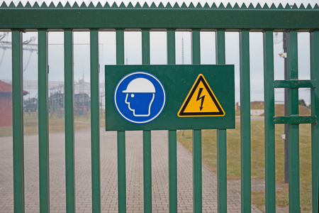 yellow beware: sign on fence high voltage