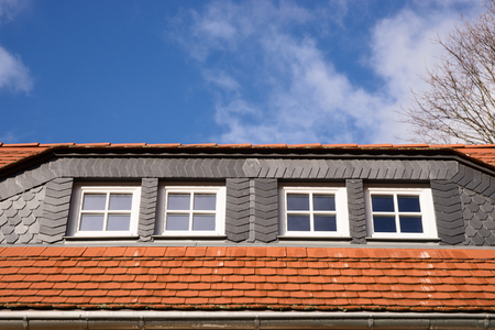 roof windows: Closeup of red and black roof tiles with windows