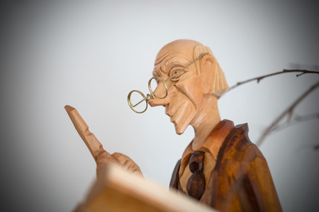 wagging: Wood sculpture, old man with glasses and wagging finger Stock Photo