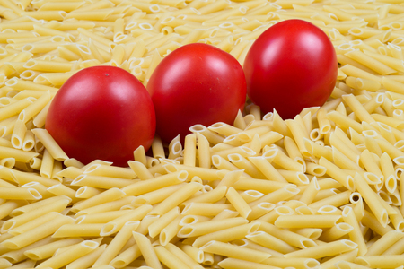 rotini: Pasta Penne texture background with red tomatoes Stock Photo