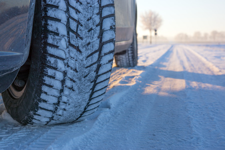 Winter tyre on the road covered with snow