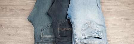 Three different blue jeans on wooden background Stock Photo