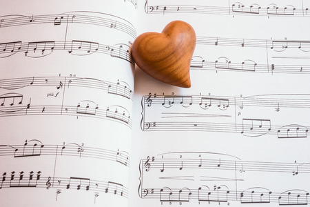 Wooden heart on a sheet of music, love song
