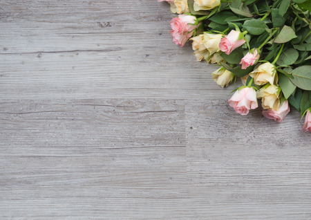 pink rose petals: Pink and yellow roses bouquet over wooden table