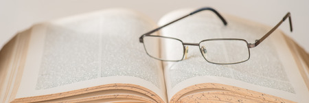 bibliophile: antique book with glasses, selective focus