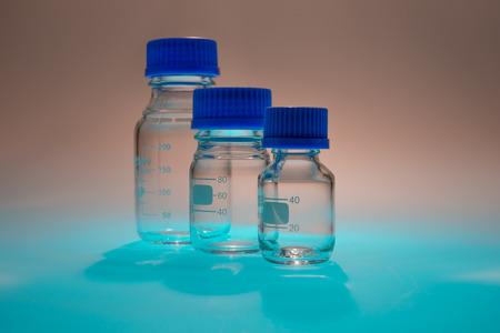 hypothesis: Glass laboratory apparatus isolated on blue table with brown background Stock Photo