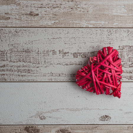 Red wood heart on rustic wooden background