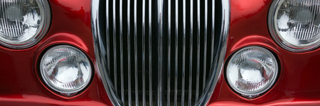 grille: Vintage car detail with red color - chrome grille