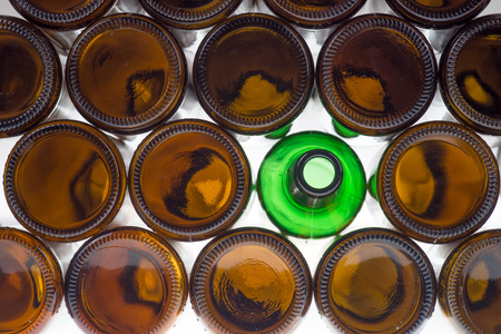brown bottles: Glass green bottle among brown bottles. Concept of difference Stock Photo
