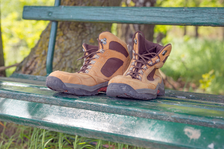 hillwalking: Hiking shoes on green bench in the forest