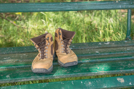 foot gear: Hiking shoes on green bench in the forest