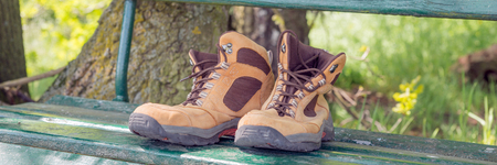 hiking shoes: Hiking shoes on green bench in the forest