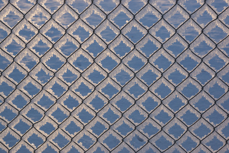 chainlink fence: Chain-link fence with snow, winter background, abstract urban design