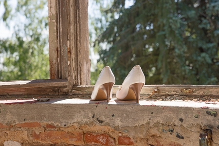 urban decline: White High Womens shoes in the window of an abandoned building