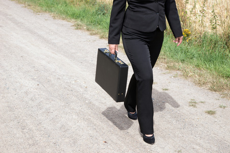 black briefcase: Woman on the dirt road with black briefcase