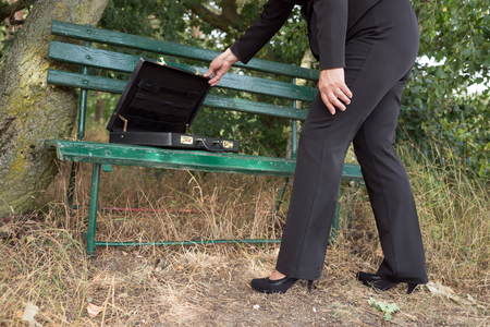 criminally: Businesswoman opens briefcase on a park bench