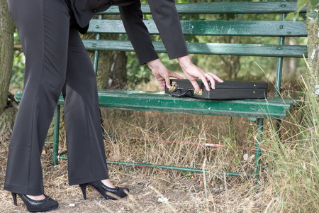 disclose: Businesswoman opens briefcase on a park bench