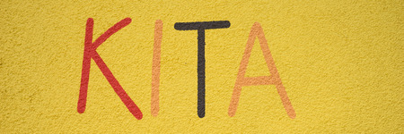 kita: german word Kita on the yellow wall
