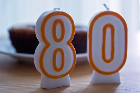80th: Birthday candles number eighty on the wooden table