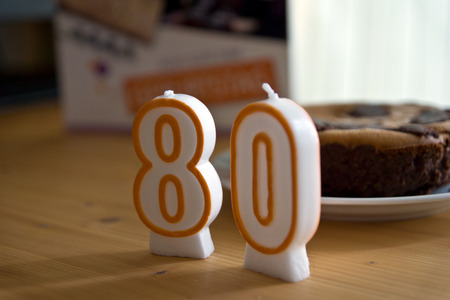 eighty: Birthday candles number eighty on the wooden table
