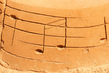 Drawn musical notes on a sandy beach Stock Photo
