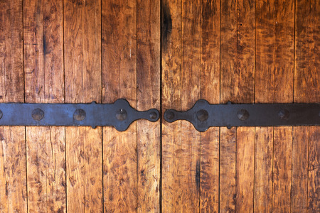 Fragment of closed old wooden gate with metal fittings