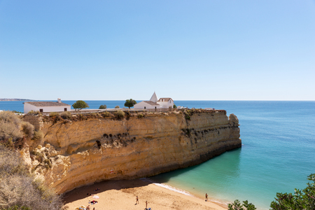 senhora: Chapel of Nossa Senhora da Rocha on top of the spectacular cliffs on Nova Beach. Algarve Stock Photo