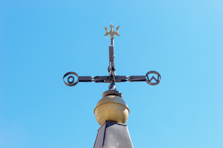 windward: Old weathervane against a blue sky, east and west