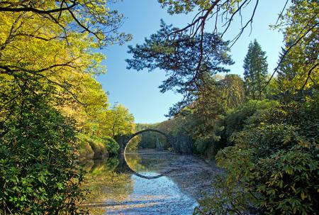 keystone: Arch Bridge in Kromlau, Saxony, Germany. Autumn in Park. Rakotz bridge in Kromlau